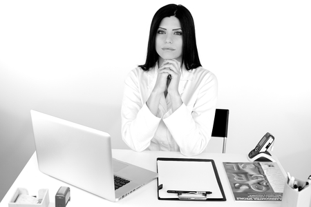 Gorgeous woman doctor sitting at desk looking photo