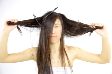 Cute asian woman unhappy about her long hair