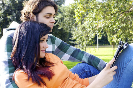 Gorgeous couple enjoying technology and wireless connection with tablet photo