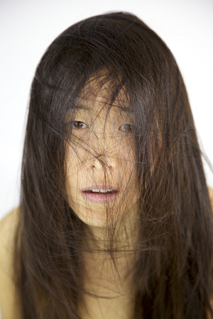 Asian woman looking unhappy with messy long hair photo