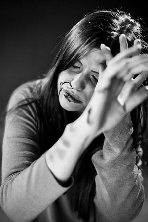 mujer golpeada: Mujer con moretones y sangre sentado desesperada
