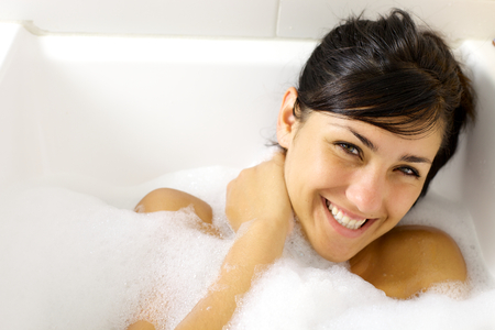 Cute young woman smiling in bath tub full of foam
