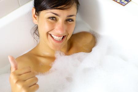 belle brunette: Couper jeune femme en s'amusant dans une baignoire Banque d'images