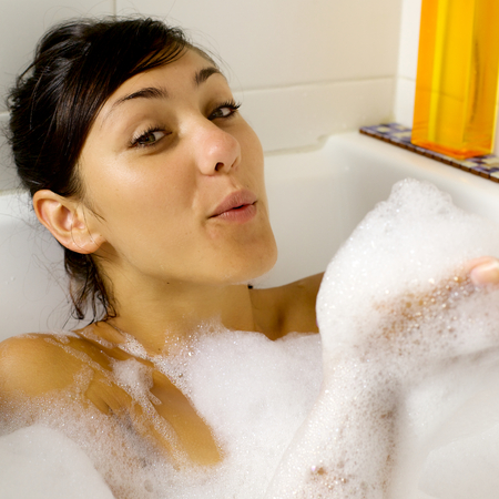 Blowing foam in bath tub having fun photo