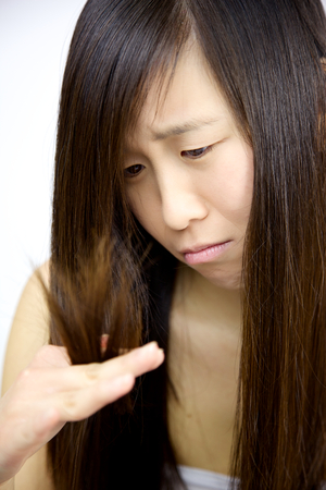 Unhappy asian woman looking desperate destroyed long hair photo
