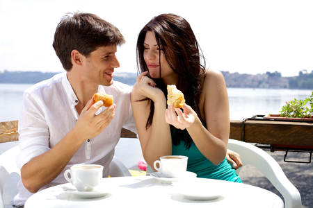 Happy couple eating cake in hotel in front of lake in Italy 版權商用圖片