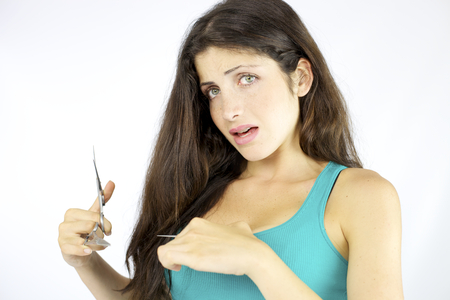 Woman with scissors in hand going to cut long hair photo