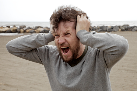 Angry crazy furious man shouting holding head with hands photo