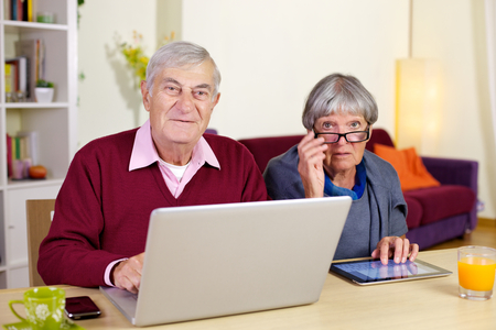 Happy elderly couple having fun with technology tablet and pc photo