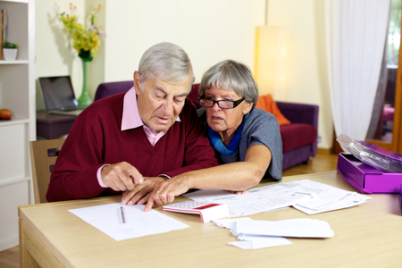 man holding money: Senior couple at home calculating bills