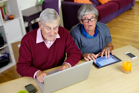 Mature couple having fun with tablet and computer photo