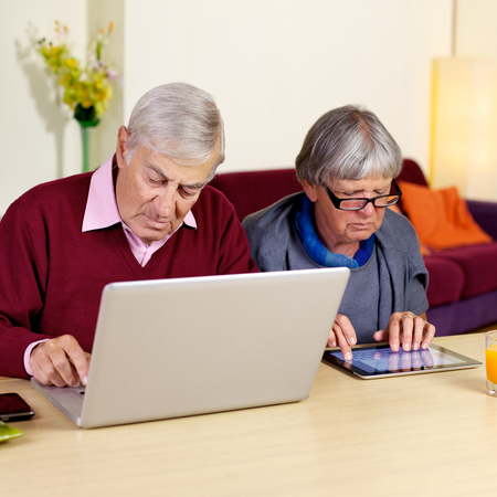 Senior man and woman at home writing email and on social network photo