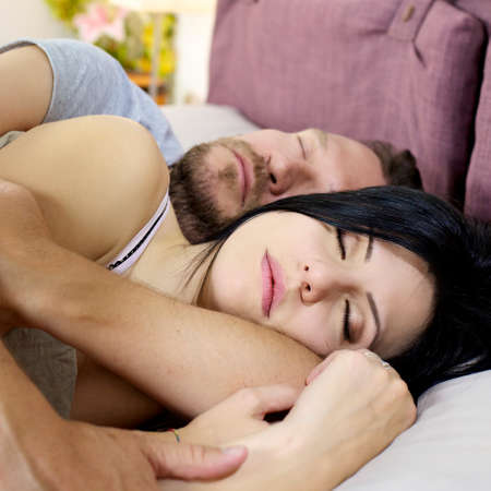 Beautiful couple in vacation sleeping in bed photo