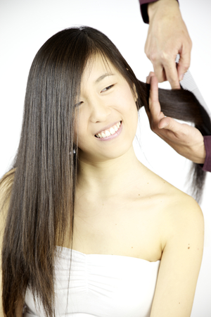 combed: Happy asain woman getting long hair combed by professional hairstylist