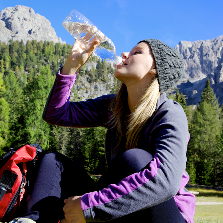 attractive blonde girl drinking water sitting on grass in front of mountain after a walk photo