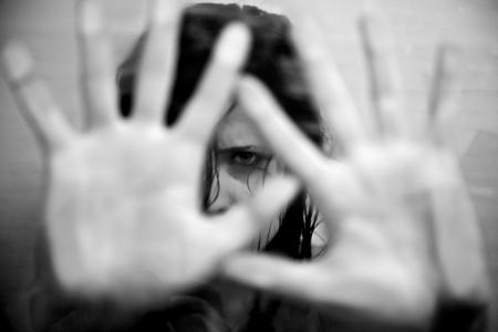 Trieste vrouw bang zetten handen in de voorkant van het gezicht