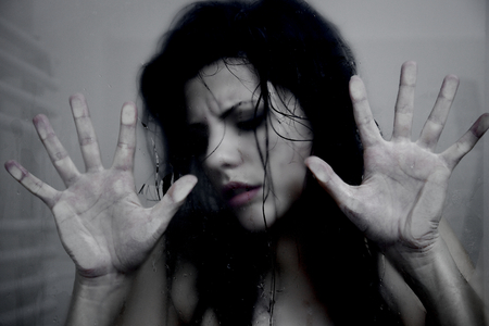 Scared woman trapped in glass wet photo