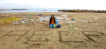 Young desperate woman not able to clean beach photo