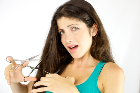 Unhappy woman with scissors in hand stressed about ruined hair