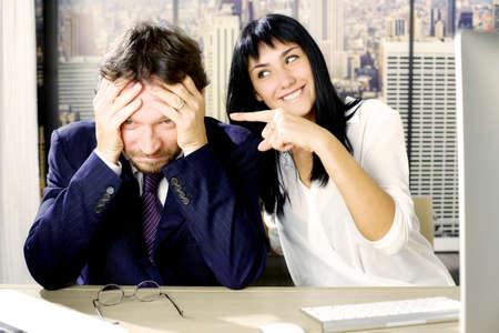 Young happy business woman making fun of sad man photo