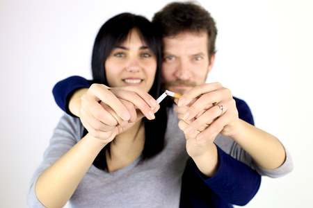 smoker: Man and woman breaking cigarette quitting smoke Stock Photo