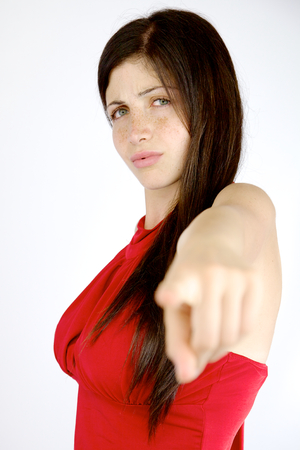 Unhappy beautiful woman with freckles pointing finger photo