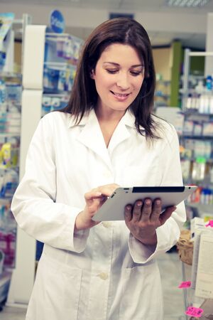 Beautiful female doctor working in pharmacy photo