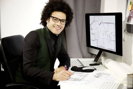 architect office: Young handsome man in office designing interior of house Stock Photo