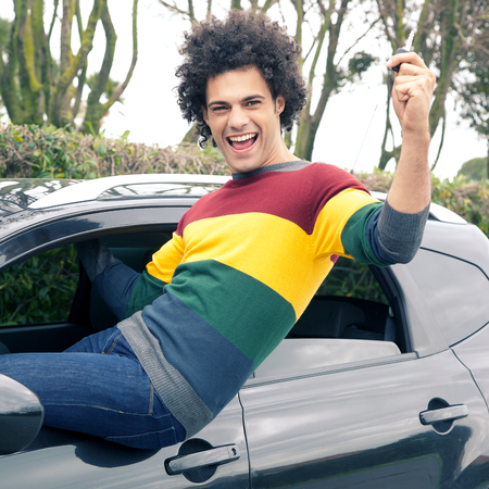 Man sitting out of window of new car photo