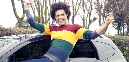 глядя на камеру: Прохладный, красивый мужчина смотрит камера счастлив, удерживая нажатой клавишу автомобиля Фото со стока