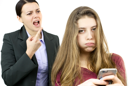Mother yelling at daughter with phone Stock Photo