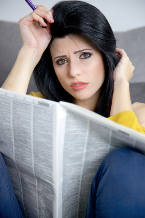 looking for a job: Woman unhappy looking for a job on newspaper