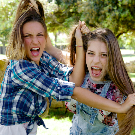 pulling beautiful: Two blond teenagers angry looking camera