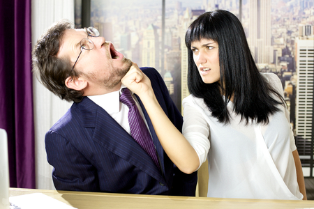 Angry woman punching business coworker in office