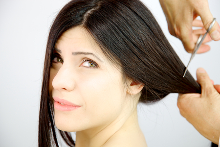 fearing: Beautiful woman with closed eyes fearing hairstylist cutting long hair with scissors closeup Stock Photo