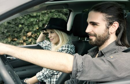 cool guy: Cool couple in car with man driving happy, looking ahead