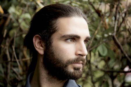 closeup oh serious handsome man with beard and long hair