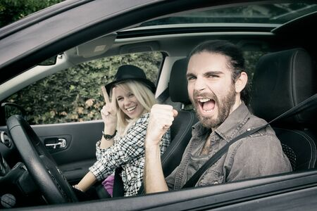 smiling happy young couple in car ready to go on a road trip Banque d'images