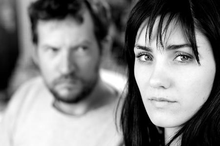 violencia intrafamiliar: Infeliz triste novia con el novio miedo en el fondo blanco y negro Foto de archivo