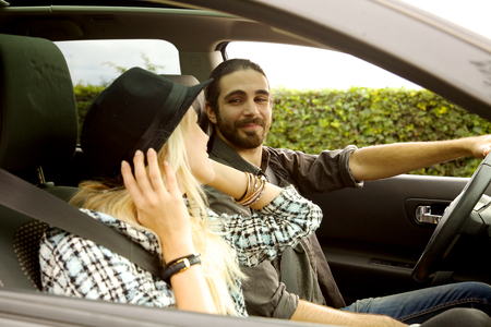 going in: Cool couple in car going in vacation Stock Photo