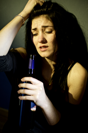 whine: Woman drinking from bottle of whine Stock Photo