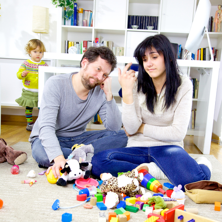 mess: Cute little girl making mess with toys while parents are very tired Stock Photo