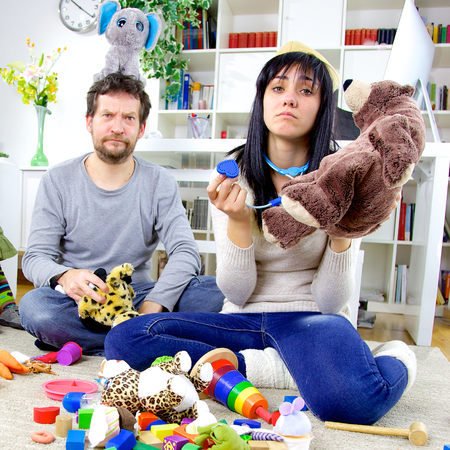 chaos: Man and woman with daughters toys everywhere Stock Photo