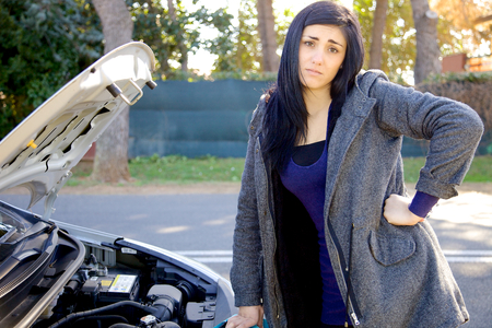 Unhappy woman looking broken engine of car