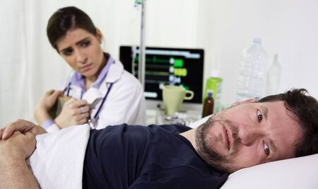 healt: Very ill man in hospital bed, almost crying for his healt condition. He looks desperate. Doctor is sitting next to him