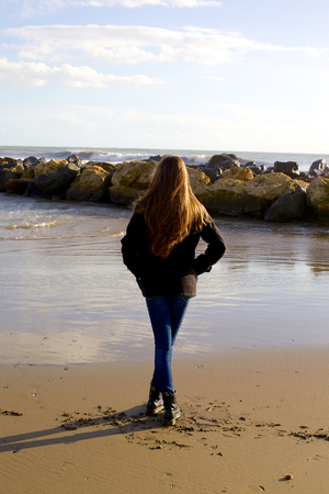 Unhappy young woman sad in front of rocks and ocean in winter