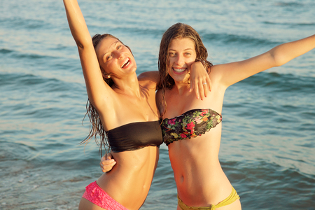 Happy girls with long hair feeling air sitting on sand Stock Photo