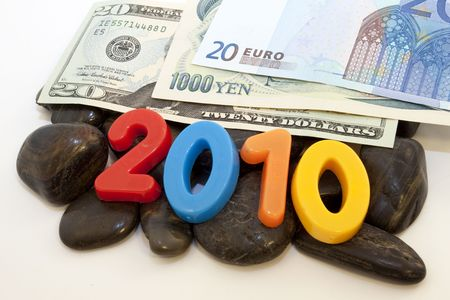 Intertwined, difficult nature of the global economy is reflected in the images of euro, yen, and dollars on the rocks accented by colorful numbers, 2010; Stock Photo - 7252880