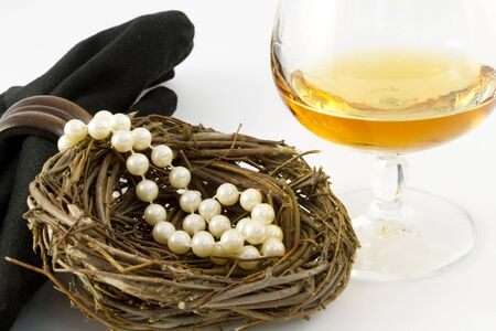 A feminine nest egg of pearls presented with a glass of brandy