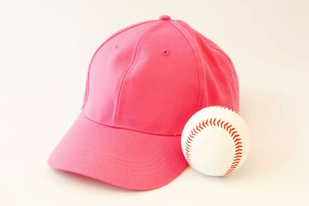 Pink baseball cap next to baseball reflects a feminist involvement in our national pastime; photo